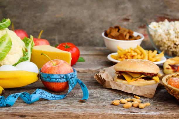 fastfood e alimentos saudáveis em fundo de madeira velho. conceito de escolher nutrição correta ou de comer lixo. - junk food - fotografias e filmes do acervo