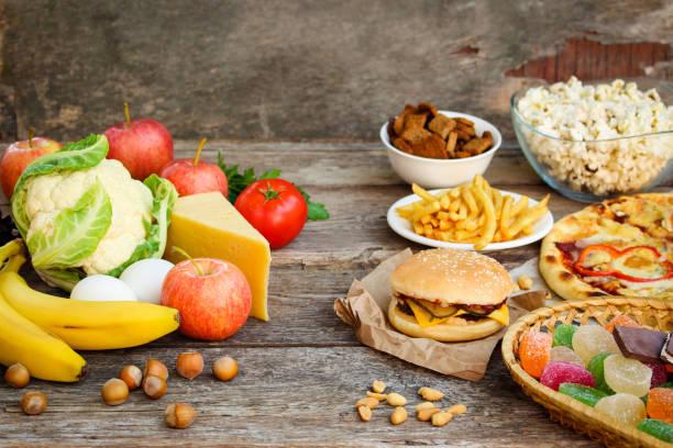 速食和老木背景上的健康食品。選擇正確的營養概念或垃圾吃。 - 不健康飲食 個照片及圖片檔