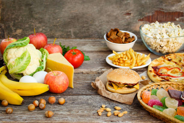 Fastfood and healthy food on old wooden background. Concept choosing correct nutrition or of junk eating. stock photo