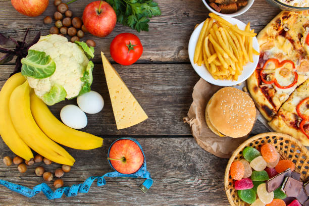 Fastfood and healthy food on old wooden background. Concept choosing correct nutrition or of junk eating. Top view. stock photo