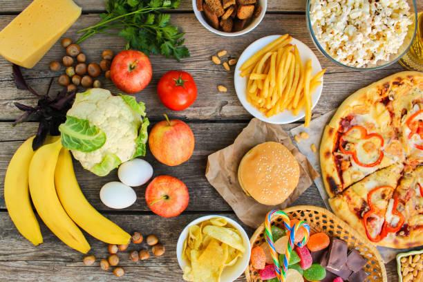 fast-food en gezond voedsel op oude houten achtergrond. concept kiezen van de juiste voeding of ongewenste eten. bovenaanzicht. - snack stockfoto's en -beelden