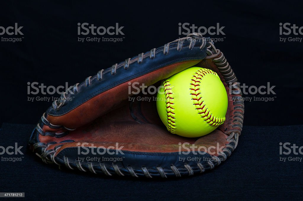 A dark colored fastpitch softball catchers mitt with a yellow...