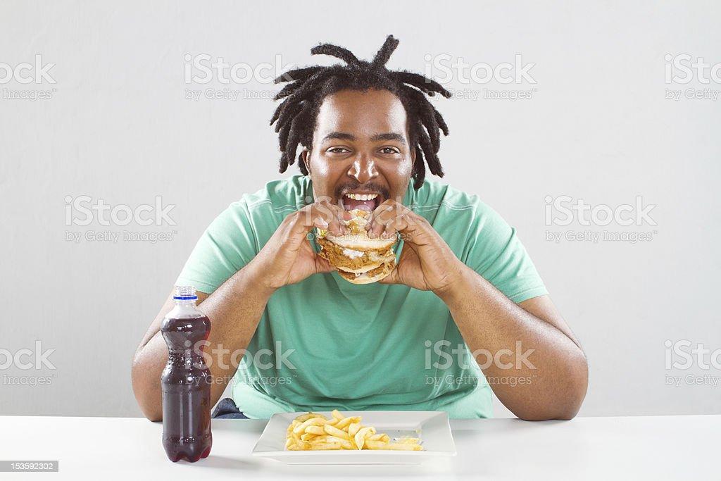 fat african american man eating hamburger stock photo