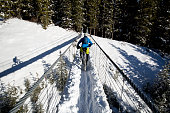 A man goes for a winter fat bike ride over a suspension bridge in the Rocky Mountains of Canada. Fat bikes are mountain bikes with oversized wheels and tires for riding on the snow. The rider is wearing a cycling helmet and warm winter bicycle clothes.