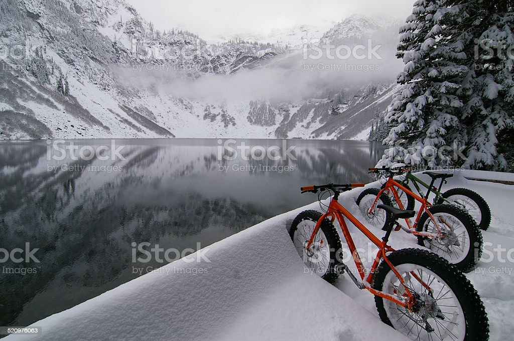 Fat bikes parked in a snow bank at a lake stock photo