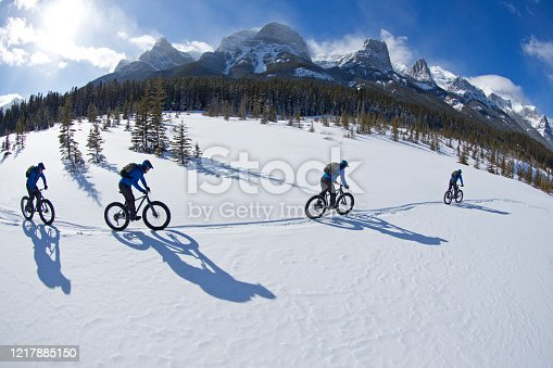 A digital composite photo of a young man going for a winter fat bike ride at the Canmore Nordic Centre in Alberta, Canada. Fat bikes are mountain bikes with oversized wheels and tires for riding on the snow. He wears a cycling helmet, carries a backpack and wears warm winter cycling clothes.