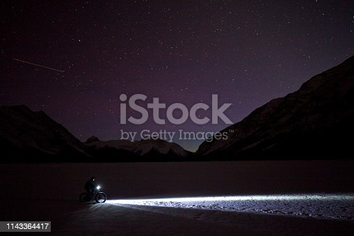 A man goes for a nighttime winter fat bike ride under the stars in the sky on a frozen lake in the Rocky Mountains of Canada. Fat bikes are mountain bikes with oversized wheels and tires for riding on the snow. He has lights on his bicycle to light up the trail.