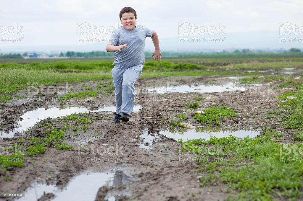 fat boy running in   field among the mud and puddles stock photo