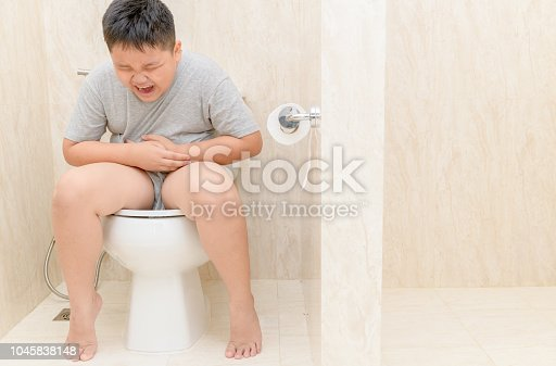 istock fat boy suffer stomach and sit in toilet, 1045838148
