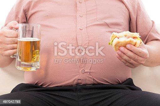 istock fat business man holding beer mug and hamburger 497042793
