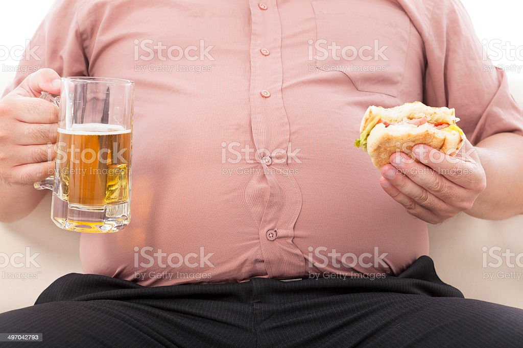 fat business man holding beer mug and hamburger stock photo