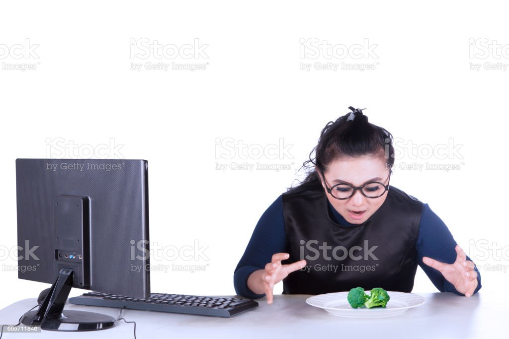 Fat businesswoman wants to eat broccoli stock photo