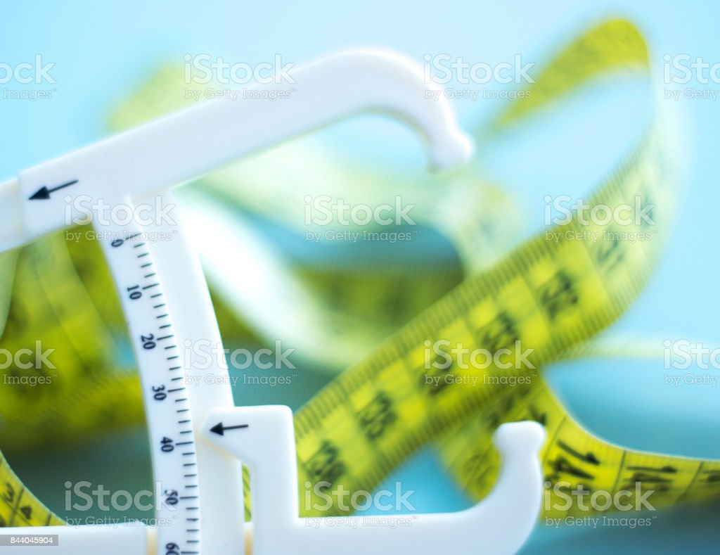 Fat caliper and measuring tape used to measure waistline, bodyfat levels for fitness and obesity check stock photo