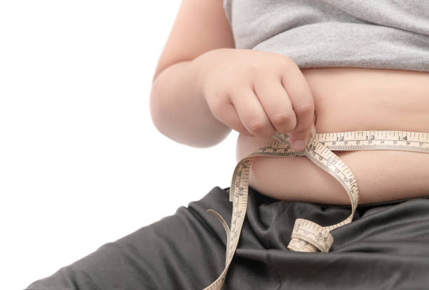 fat child check out his body fat with measuring tape - obesity foto e immagini stock