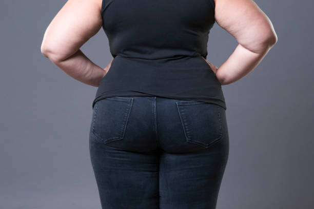 Fat female buttocks in black jeans, overweight woman body closeup stock photo
