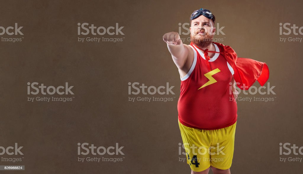 Fat funny man in a superhero costume stock photo