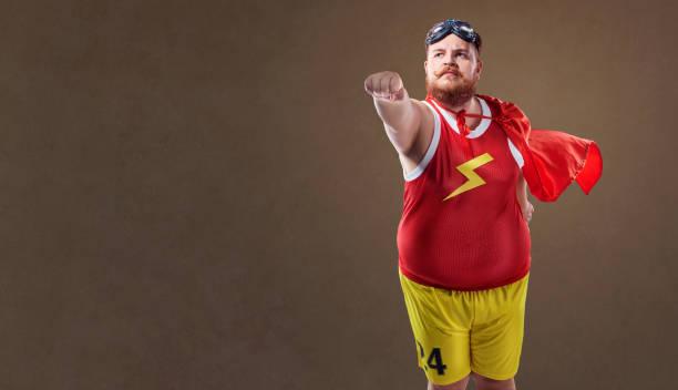 dicker lustige mann in einem superhelden-kostüm - faschingskostüme herren stock-fotos und bilder