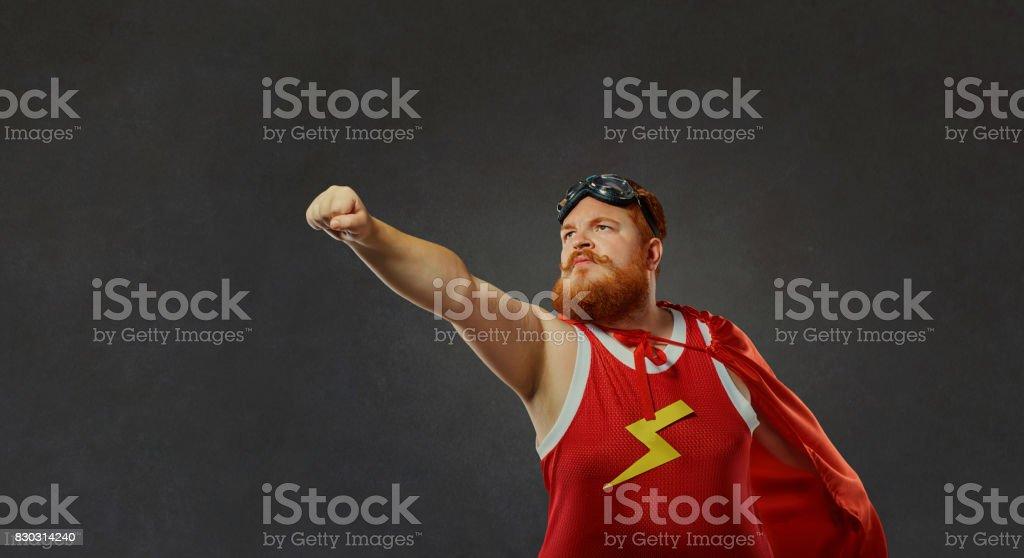 Fat funny man in a superhero costume. stock photo