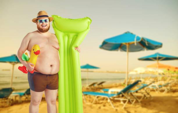 Fettlustige Mann in Badehosen mit einer aufblasbaren Matratze auf grauem Hintergrund. – Foto