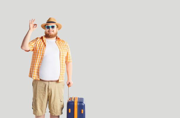 Fettlustiger Mann mit einem Koffer, der auf grauem Hintergrund schrie. – Foto