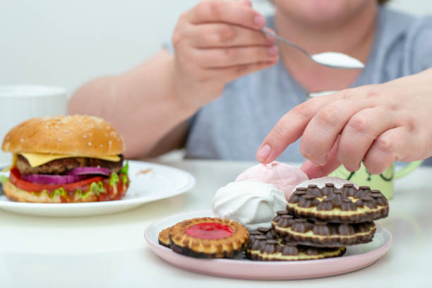 Fat girl eat a lot of sweet. Obesity of sweets. The problem excess weight. stock photo