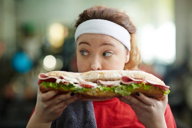 fat girl obsessing over food - gewicht schnell verlieren stock-fotos und bilder