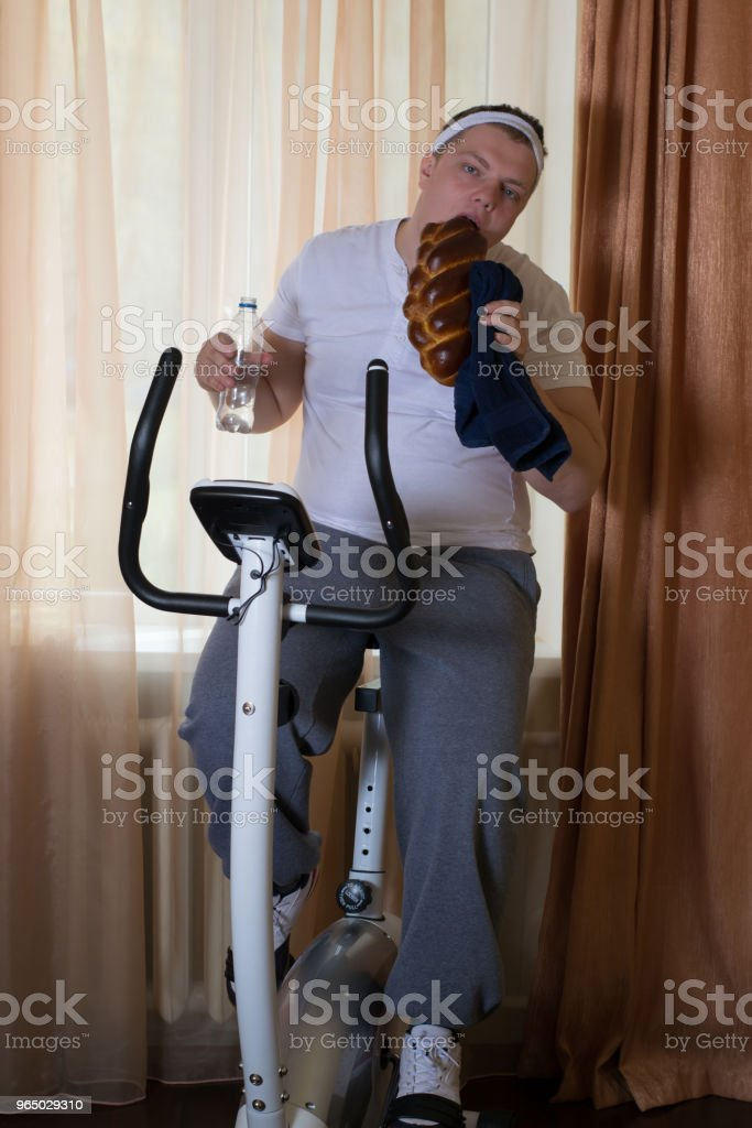 Fat guy exercising on stationary training bicycle and eating a bun royalty-free stock photo