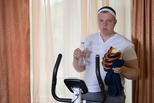 Fat Guy Exercising On Stationary Training Bicycle And Eating A Bun Stock Photo - Download Image Now