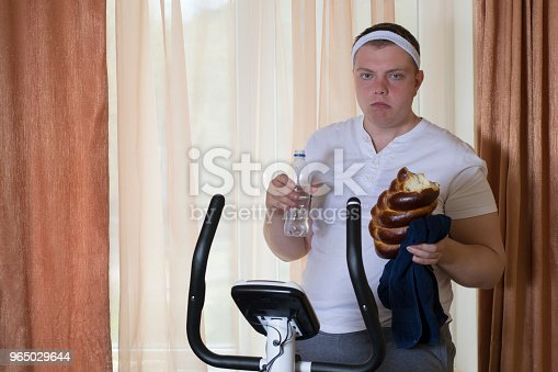 Fat Guy Exercising On Stationary Training Bicycle And Eating A Bun Stock Photo & More Pictures of Adult
