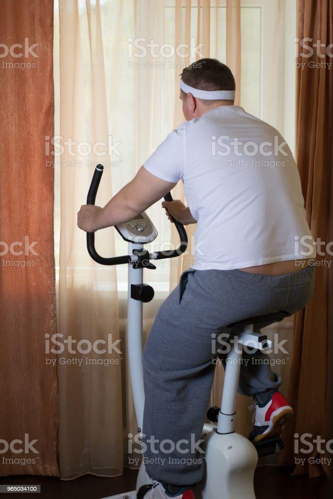 Fat guy exercising on stationary training bicycle royalty-free stock photo