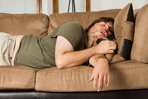 fat guy passed out hard on the couch - sloth stock pictures, royalty-free photos & images