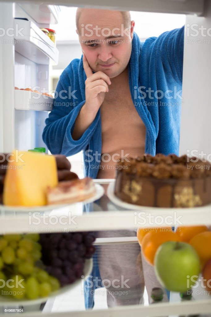 Fat guy think what to eat from fridge stock photo