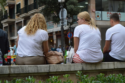 Fat happy smiling girls sitting outside with carbonated sweet drinks, the concept of overweight and diet, Palma de Mallorca, October 10, 2018