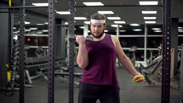 fett mann die wahl zwischen gesunden lebensstil und fast-food, richtige entscheidung - gewicht schnell verlieren stock-fotos und bilder
