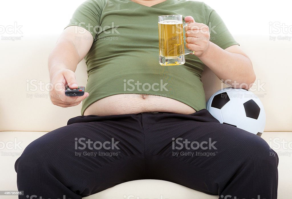 fat man drinking beer  and sitting on sofa stock photo