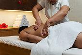Handsome fatty man during spine massage in beauty spa salon.