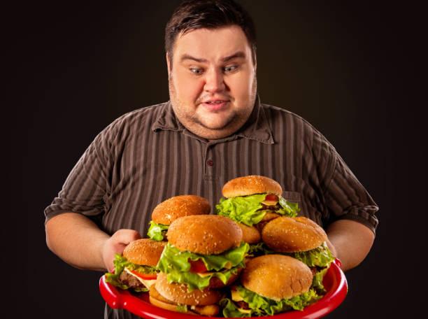 dicker mann essen fastfood hamberger. frühstück für übergewichtige. - gewicht schnell verlieren stock-fotos und bilder