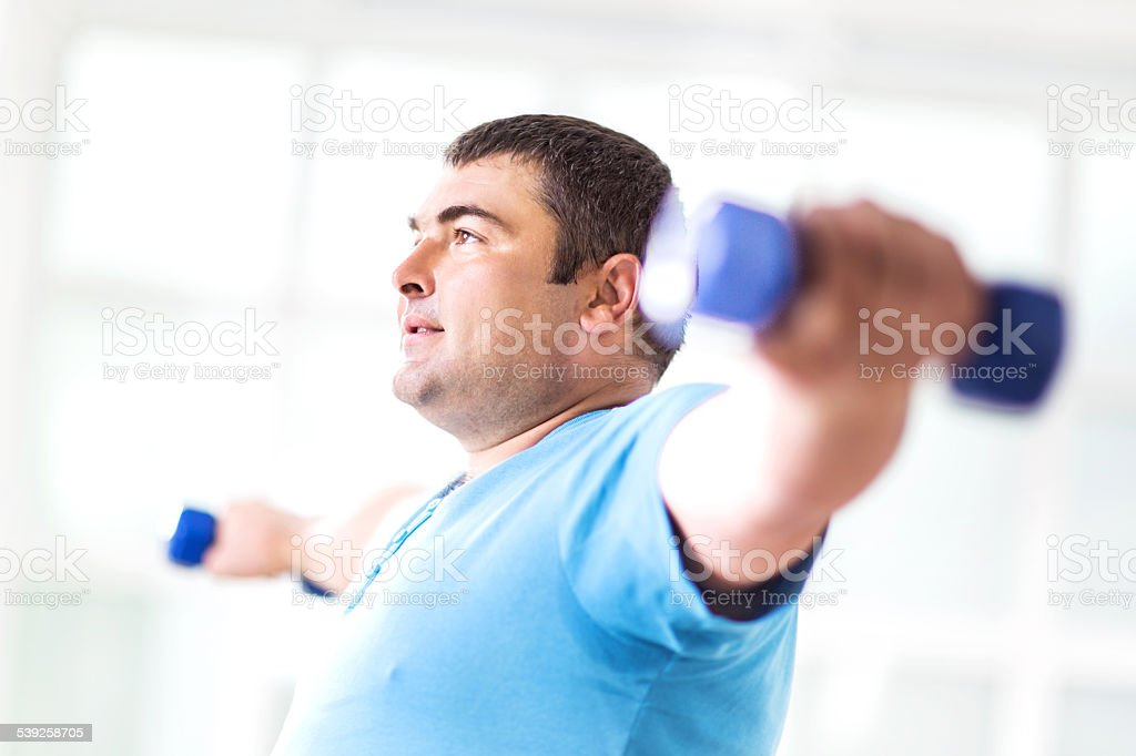 Fat man exercising with dumbbells. stock photo