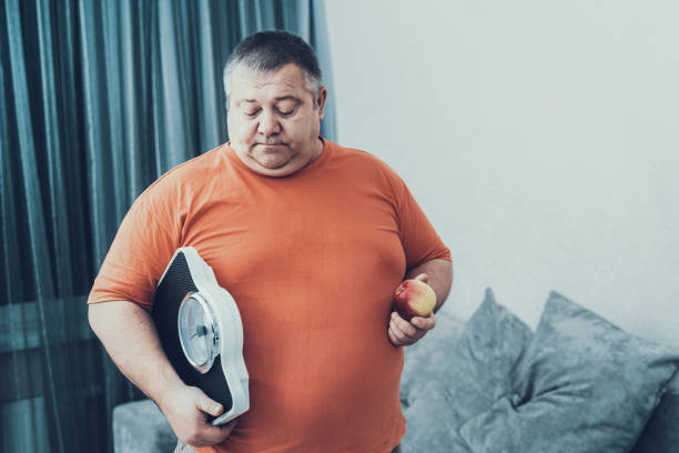 Fat Man i T-shirt with Weighter and Apple in Hands stock photo