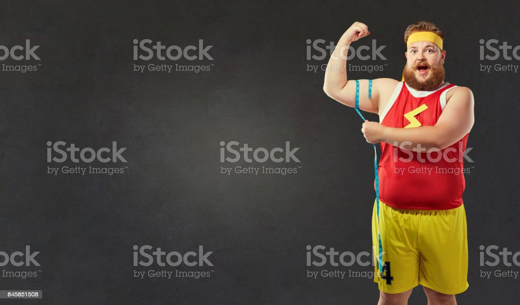 Fat man in sports clothes measures his arm with a centim stock photo