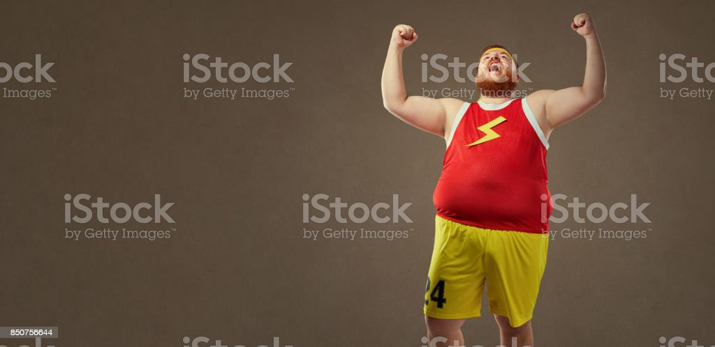 A fat man in sports clothes screams at the victory. stock photo