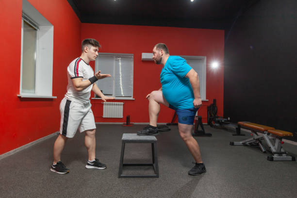 Fat man is diligently doing step-up exercise under control of a personal instructor. Overweight stock photo