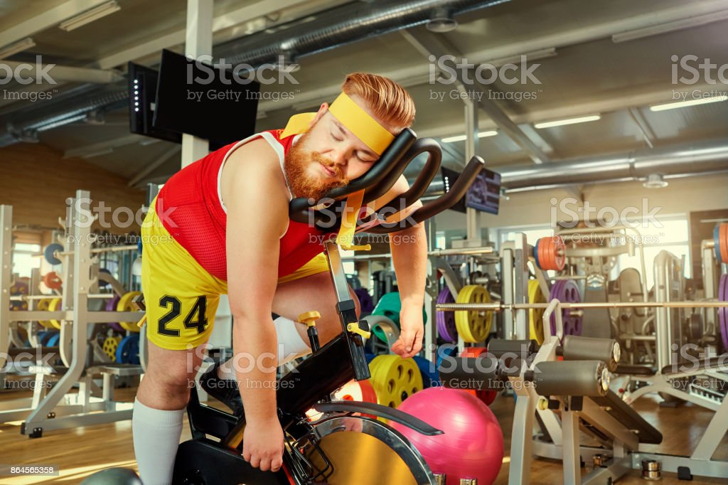 A fat man is tired on a simulator in the gym stock photo