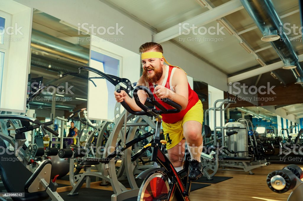 A fat man is training on an exercise bike in the gym stock photo