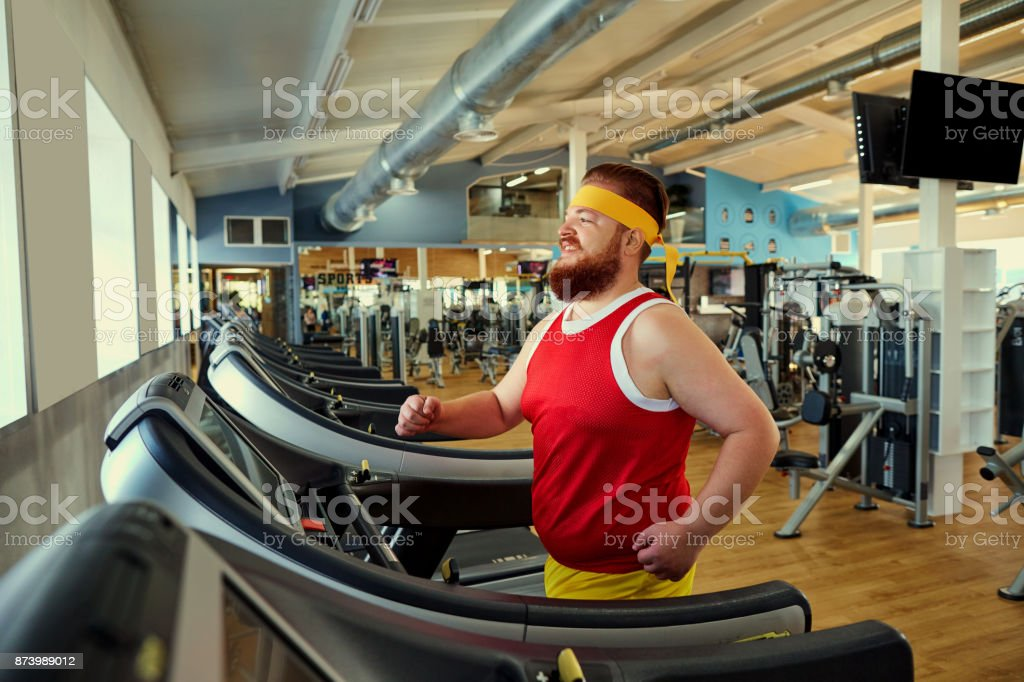 A fat man is walking along a treadmill in the gym. stock photo