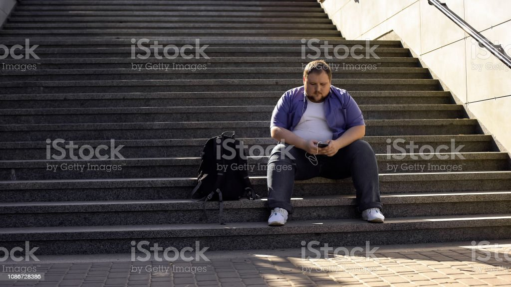 Fat man listening to music on stairs, loneliness, overweight causes...