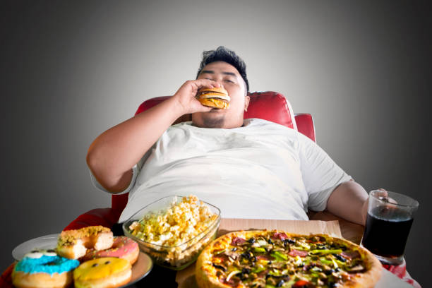 Fat man looks greedy with junk foods on the sofa stock photo