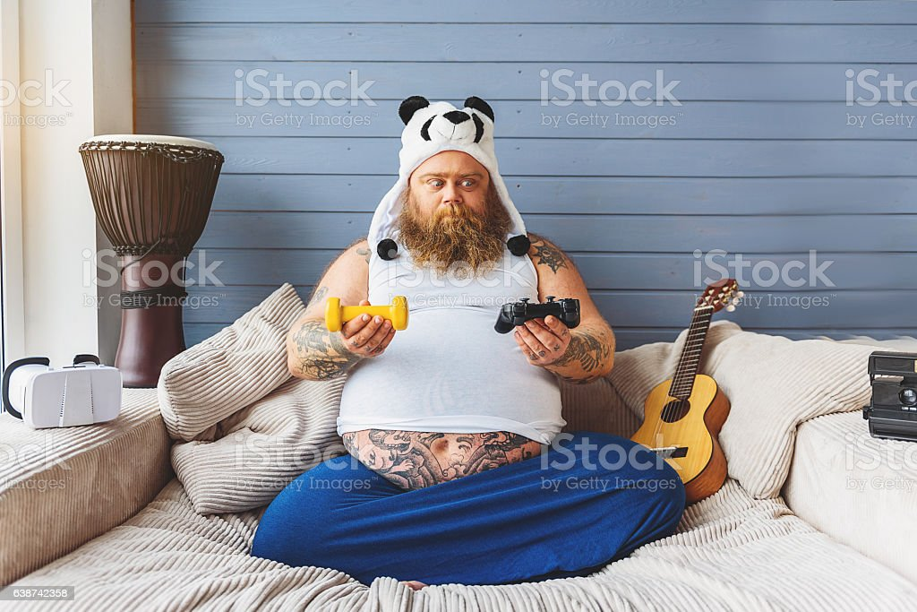 Fat man making choice between sport and game stock photo