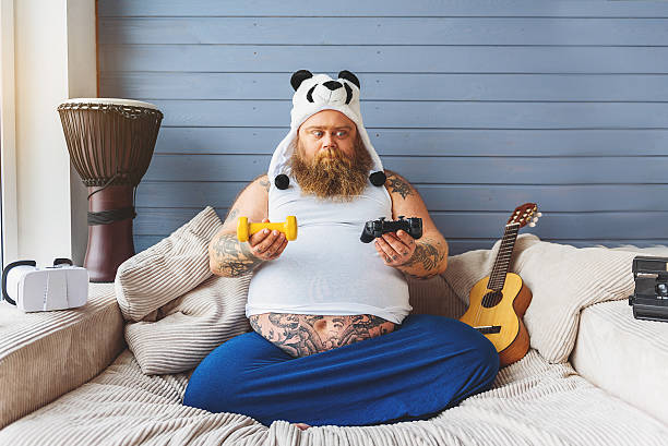 fat man making choice between sport and game - laziness stock photos and pictures