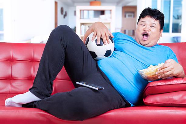 fett mann beobachten fußballspiel zu hause fühlen - gewicht schnell verlieren stock-fotos und bilder